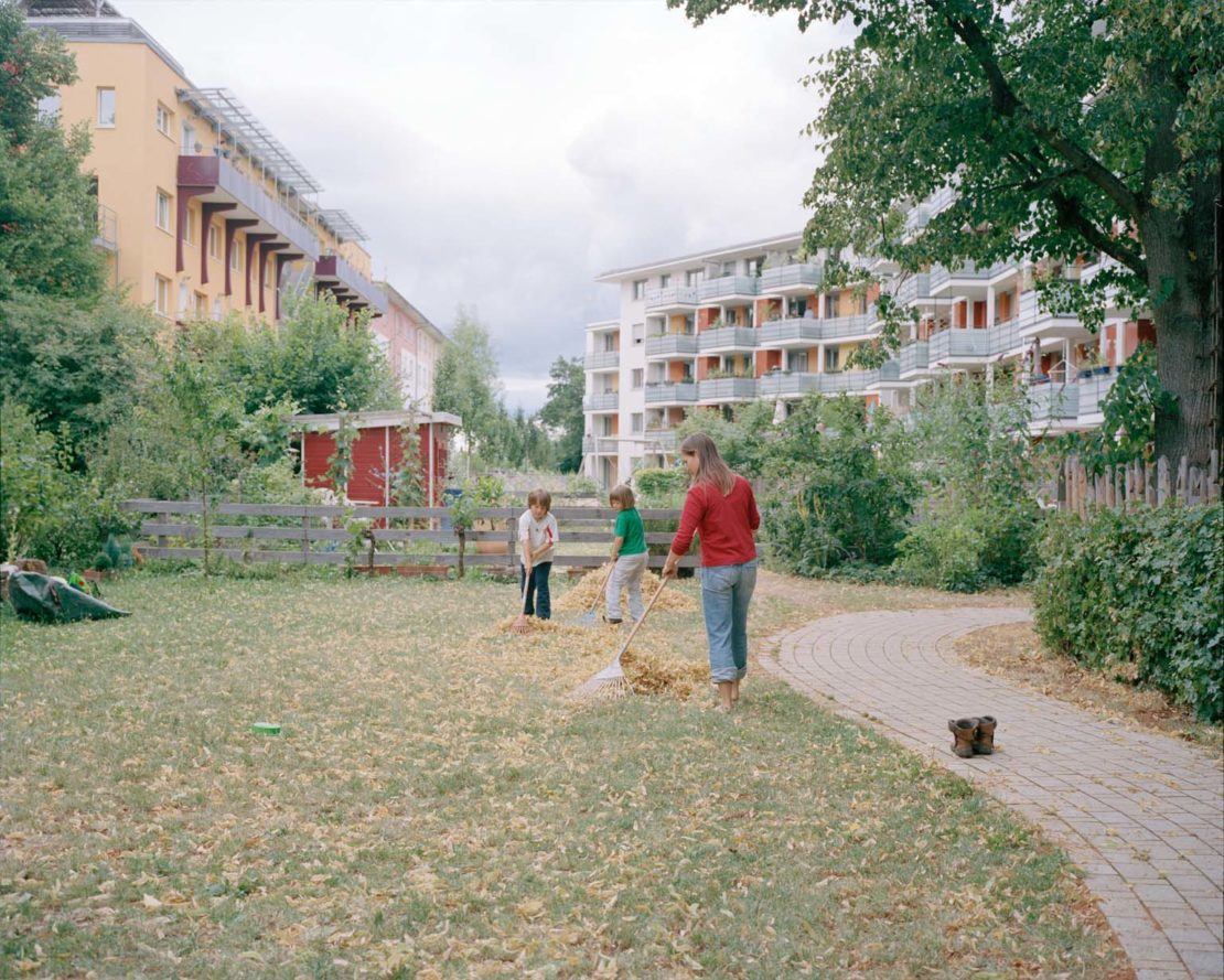 Family sweeping leaves in Vauban