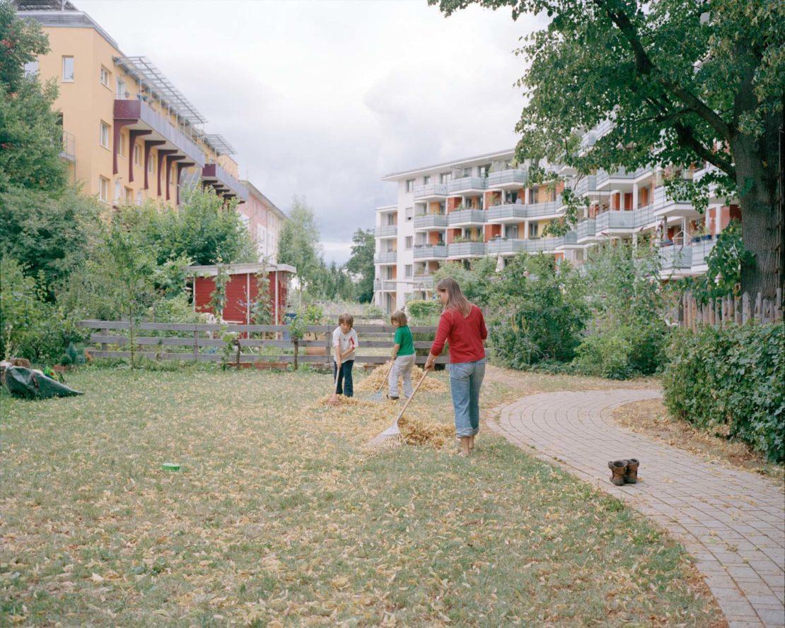 Family sweeping leaves in Vauban