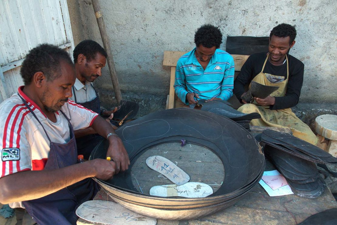 Workers cut shoe designs from discarded tyres